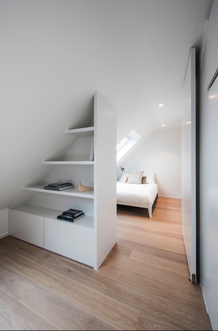 meuble sous pente sur mesure avec étagères qui sépare la chambre à coucher du reste de l'espace mansardée habitable
