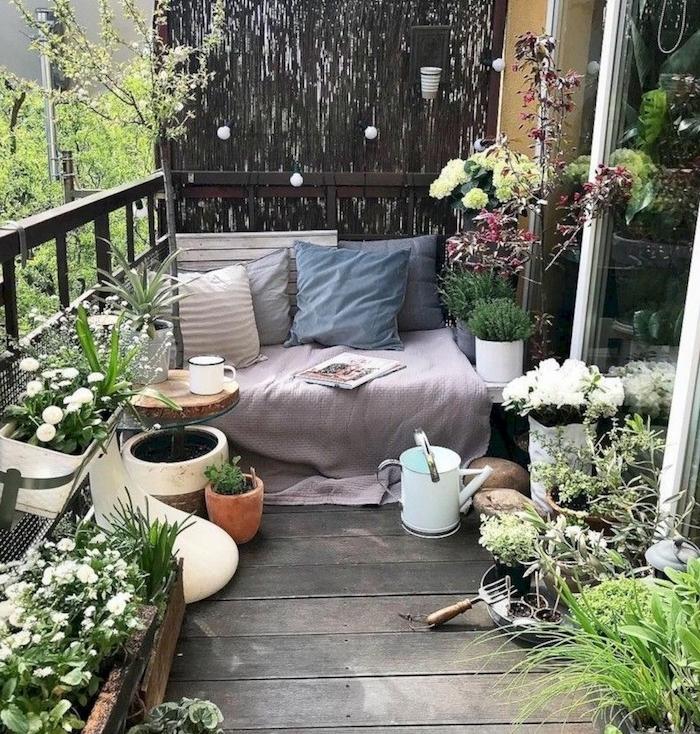 coussins décoratifs pour décorer un canapé cocooning en plein air, brise vue végétale, bacs à fleurs accrochés au garde corps et fleurs en pots par sol