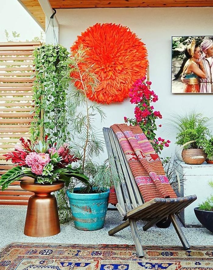 deco boheme chic de balcon, fauteuil vintage en bois, tapis oriental et decoration cercle orange, couverture colorée boheme chic, deco florale orientale, pots fleuris, plante tombante suspendue