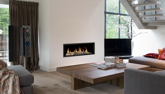 cheminée design à gaz dans un salon avec canapé et fauteuils gris, sol en parquet bois marron, escalier design
