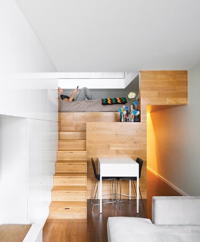 design minimaliste dans un studio tout petit en bois avec lit en dessus d une cuisine, table blanche et chaises noires, canapé gris clair