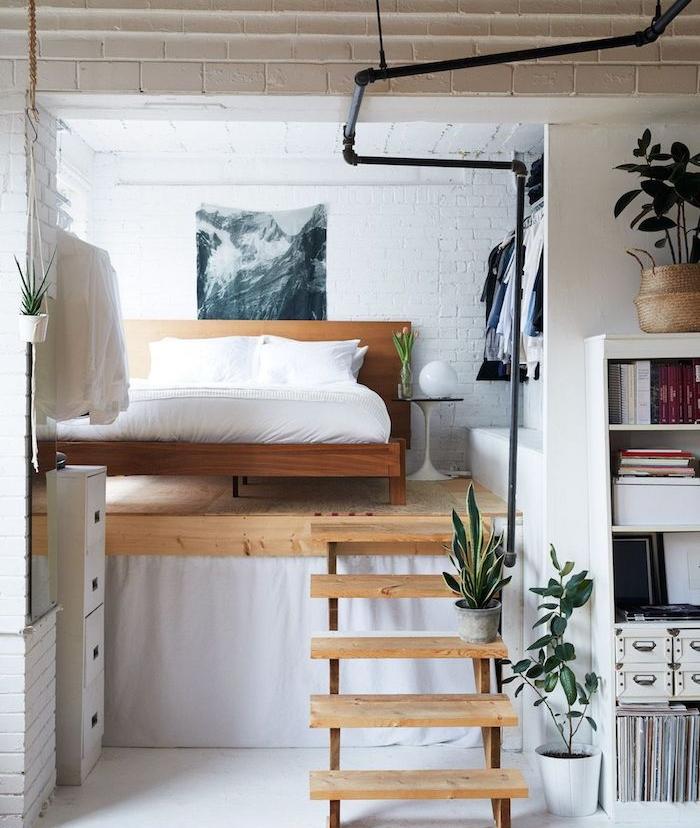 lit bois monté sur une estrade en bois avec petit escalier en bois, mur de briques blanchies, penderie ouverte, deco studio astuce gain de place