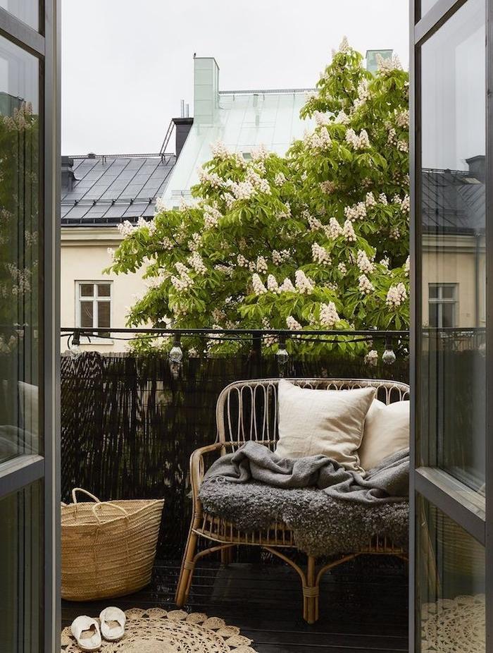 brise vue de balcon en osier, canapé en osier tressé, plaid gris et coussins blanc cassé, tapis rond oriental, panier de rangement