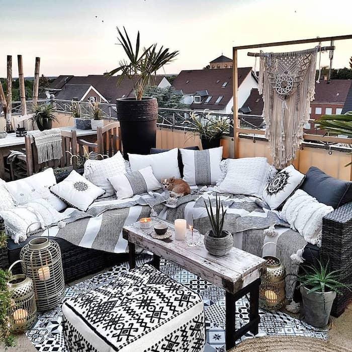 idee deco boheme choc sur un balcon sans toiture decoration amcramé, canapé d angle tressé avec couverture et coussins gris et blanc, table bois et metal, lanternes orientales