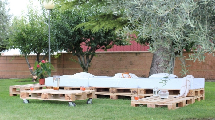 diy canapé palette fait main couvert de matelas blanc et de coussins décoratifs, modèle de table basse de jardin avec roulettes