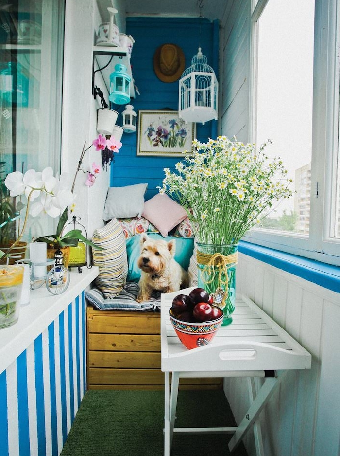 quel aménagement balcon étroit avec un fauteuil bois décoré de coussins cocooning, table pliante, mur repeint en bleu, lanternes suspendues, plantes fleuries, deco hygge exterieur, sol recouvert d herbe artificielle