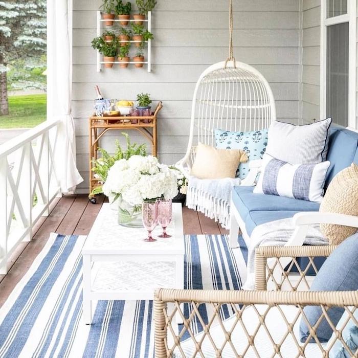 fauteuil suspendu balancelle, canapé blanc décoré de coussins bleu et blanc, table basse blanche, tapis à rayures bleu et blanc, mur végétal extérieur sur un balcon cosy