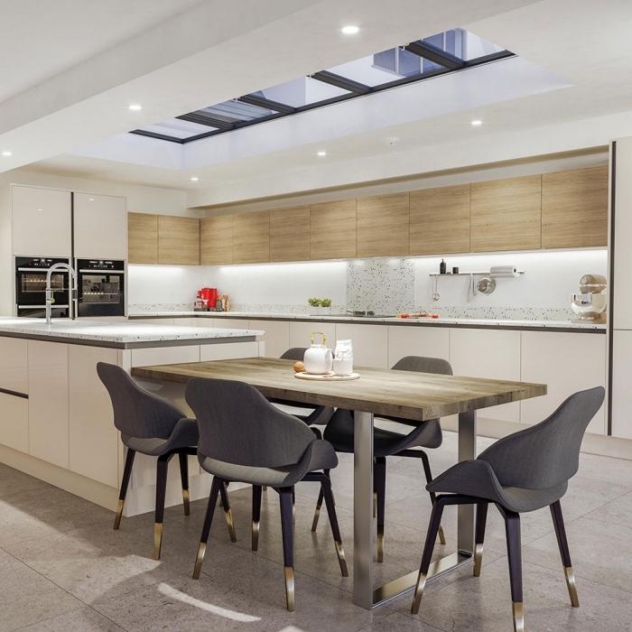 coin repas dans une grande cuisine moderne blanche et bois avec table à manger en bois brut, crédence effet pierre