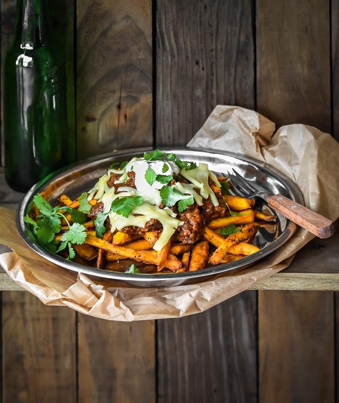 frites de patates douces à la sauce chilli et fromages, repas vegetarien facile dans une assiette façon rustique