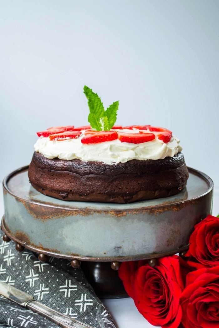 recette originale de gateau au chocolat sans farine nappé de crème fouettée et décoré de tranches de fraises