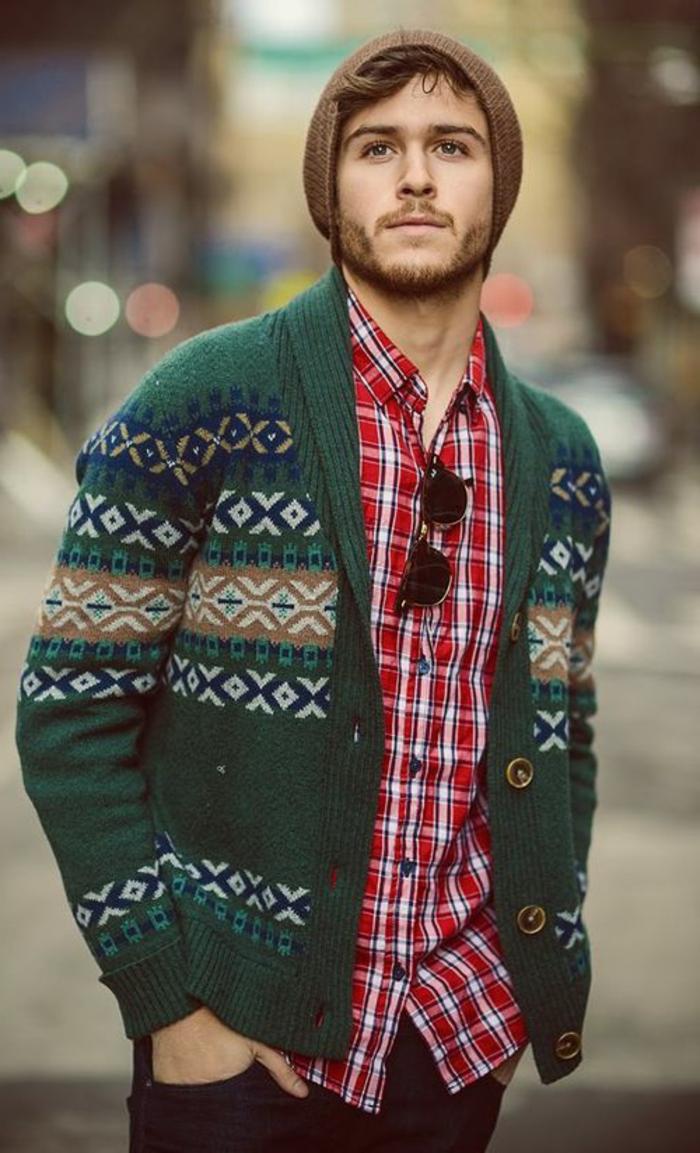 homme boho qui porte un gilet, chemise aux carreaux, bonnet tricoté marron, jean
