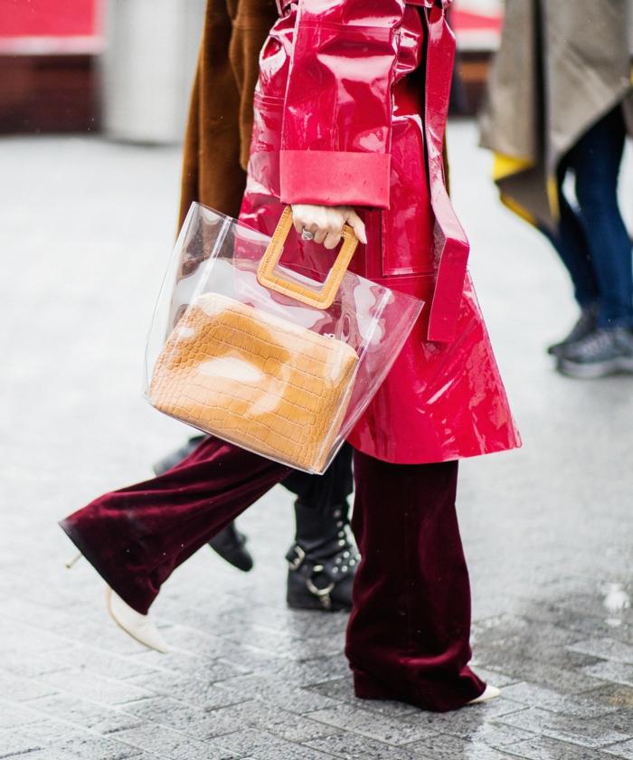 grand sac acrylique porté avec une longue veste imperméable, pantalon en daim burgundy
