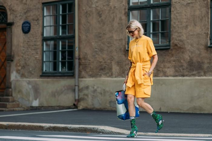 robe jaune, bottes à haut talon, grand sac a main couleur bleu, cheveux blonds, coupe carré