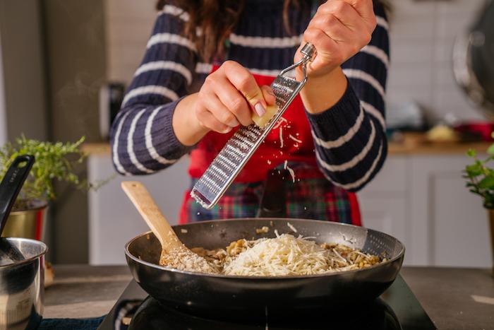 ajouter le parmesan rapé au risotto, dernier étape pour comment faire un risotto facile comme repas du soir léger