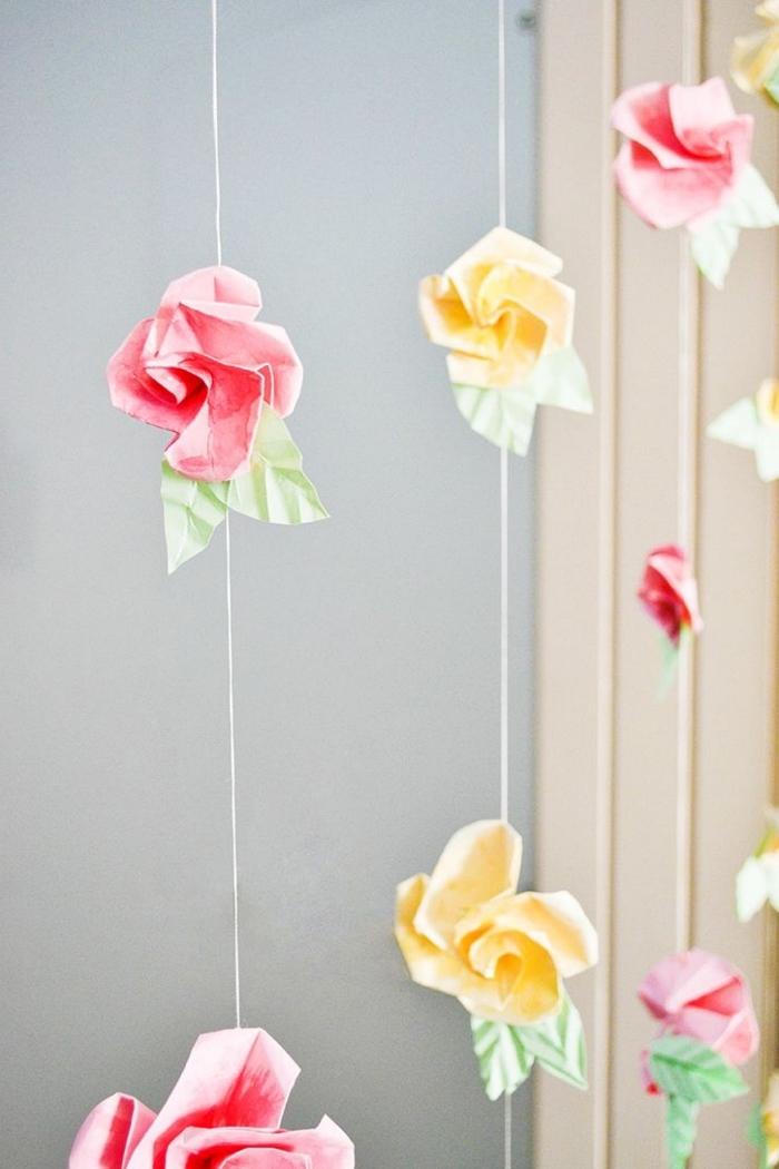 idée déco avec des roses origami enfilées sur des cordes et suspendues, modèle d'origami fleur rose avec feuilles vertes en papier