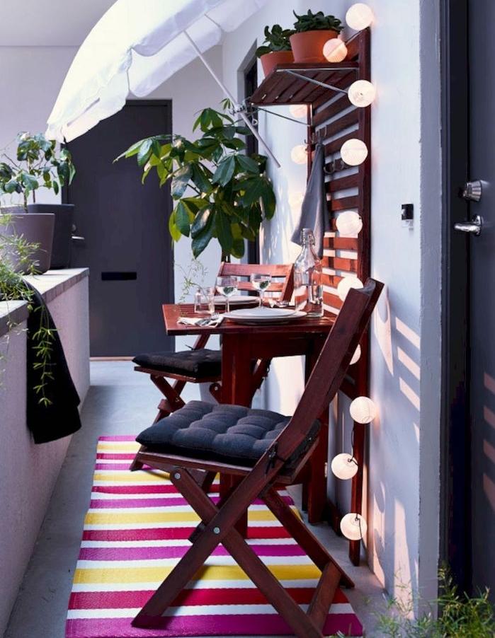 comment aménager son balcon cosy avec mur végétal extérieur en bois, guirlande boule exterrieur, table et chaises bois, tapis à rayures coloré, balcon étroit design