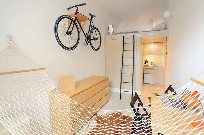 murs blancs et design minimaliste dans un studio 20 m2, kitchenette studio et armoire avec lit en dessus, hamac intérieur, bureau et commode bois