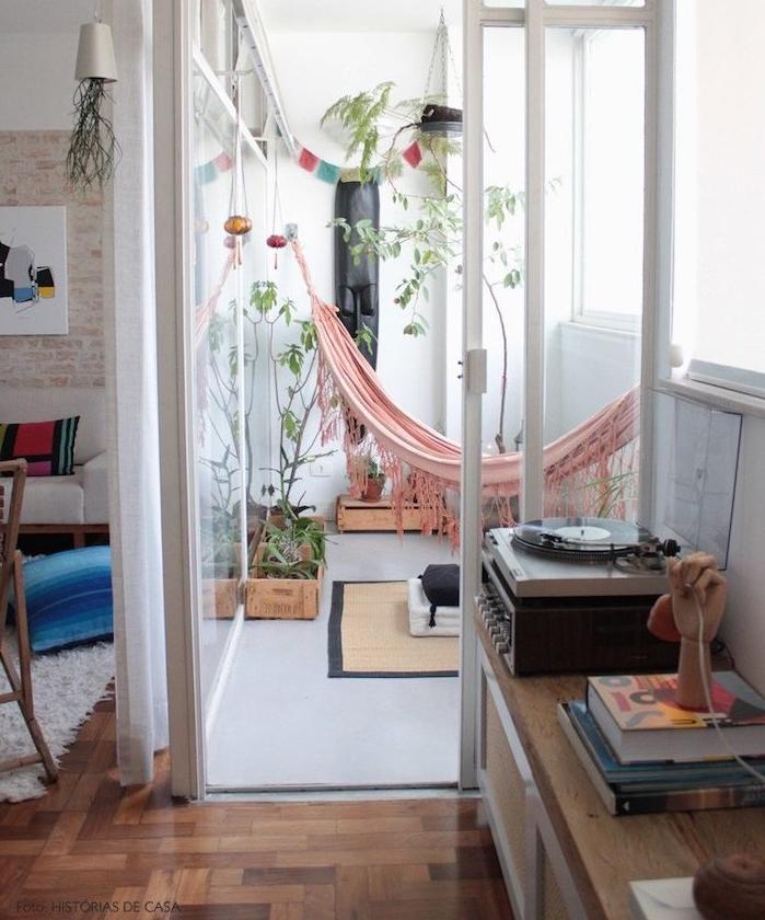 deco hippie chic sur un balcon tout petit avec hamac exterieur rose, plantes vertes, petit tapis, paroi vitrée terrasse