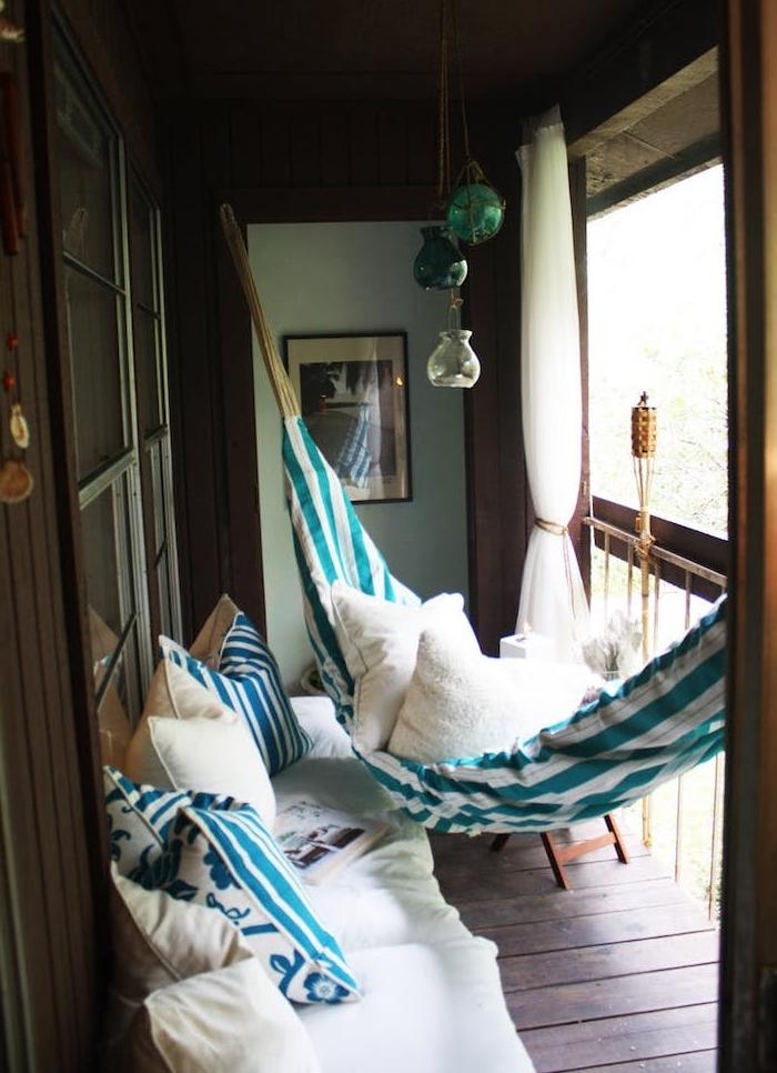 hamac d exterieur et canapé d exterieur sur un balcon habillé de bois avec plusieurs coussins décoratifs cocooning, rideau de balcon blanc