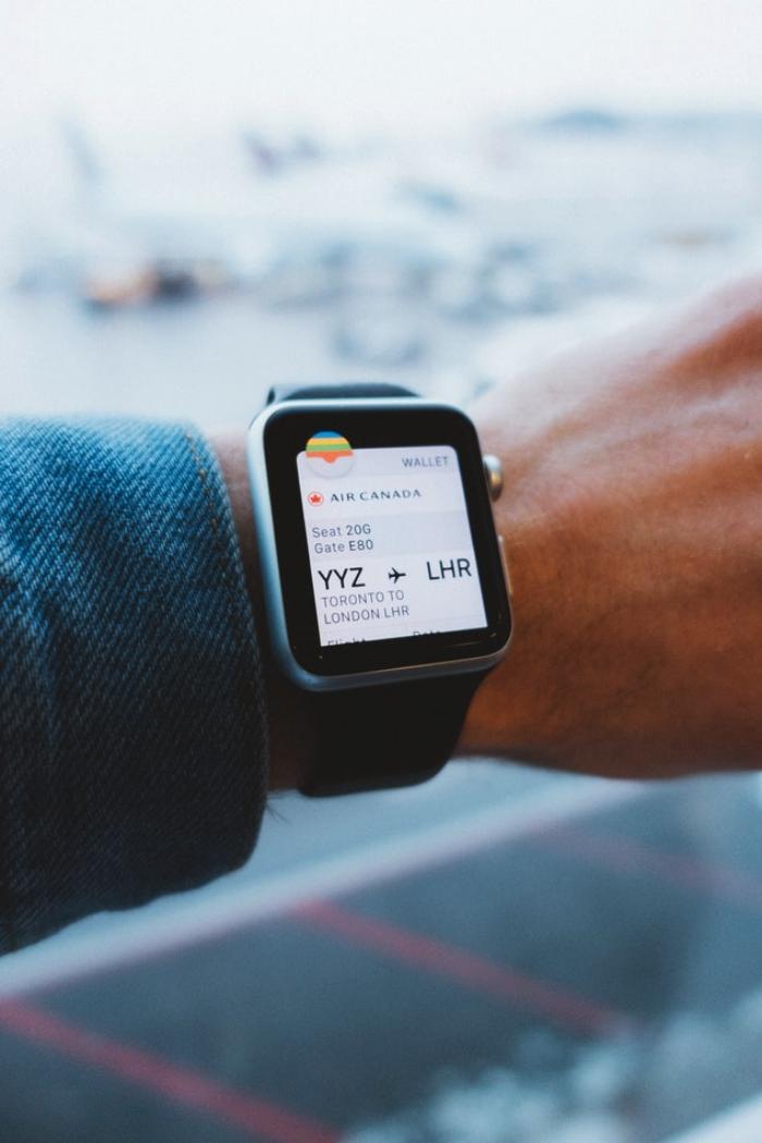 un homme regardant sa montre connectée qui porte toute l'information nécessaire sur son vol au départ