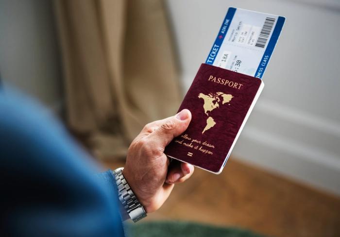 un homme tenant un passeport avec un billet d'avion, conseils pratiques pour mieux organiser son vol, se renseigner sur les documents à fournir
