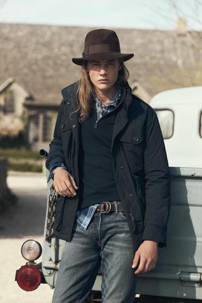 homme style boho chic, manteau noir, pull noir, chemise aux carreaux, chapeau marron, jean bleu