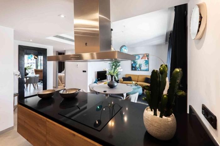 idée plan de travail cuisine moderne en noir, déco de cuisine blanche avec meubles en bois foncé et hotte en inox