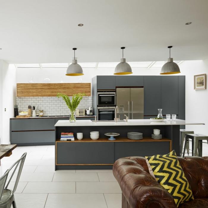 appartement studio, fauteuil en cuir, lampes suspendues girses, comptoir avec évier et espace de rangement, tabourets tolix
