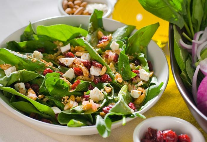 salade légère verte, radis, noix de noyer, fruits séchés, bol jaune, assiette blanche