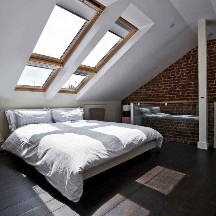 une chambre sous comble au design épuré dans un appartement mansardé, chambre à coucher mansardée baignée de lumière grâce aux fenêtres de toit