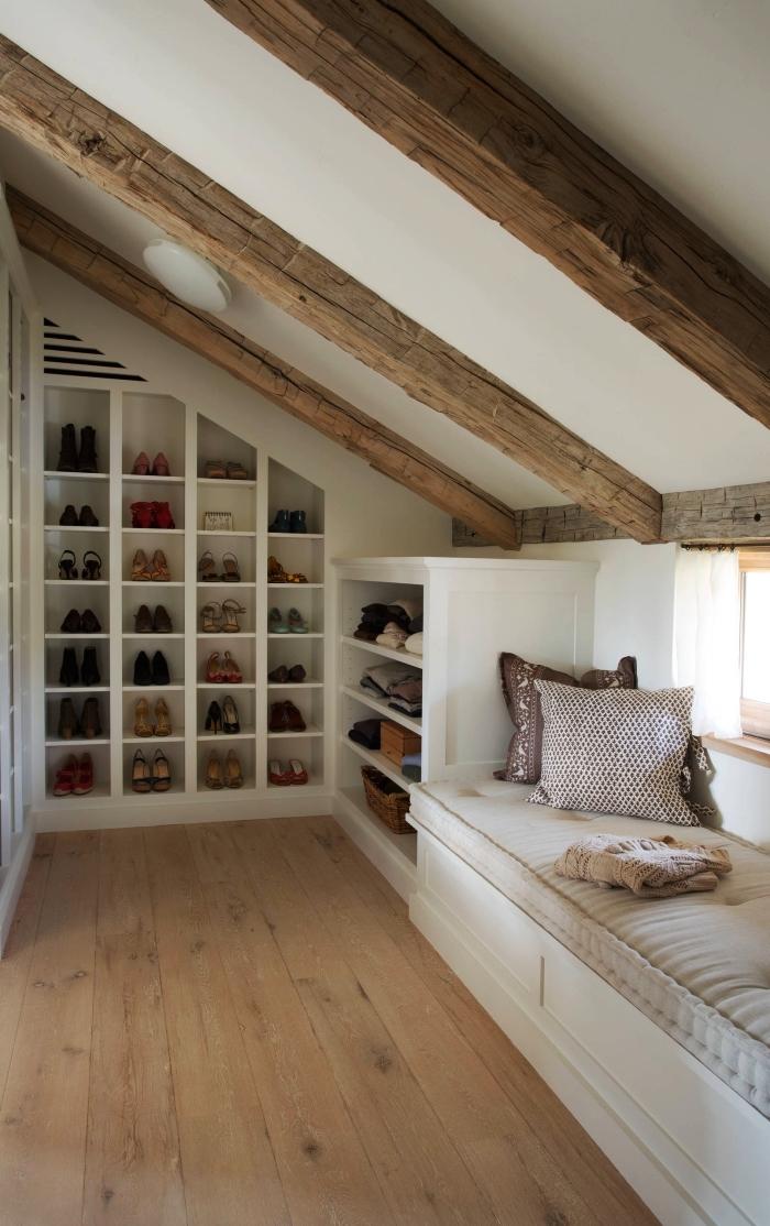 dressing sous pente aménagé dans les combles avec des étagères intégrées au mur et une banquette sous fenêtre
