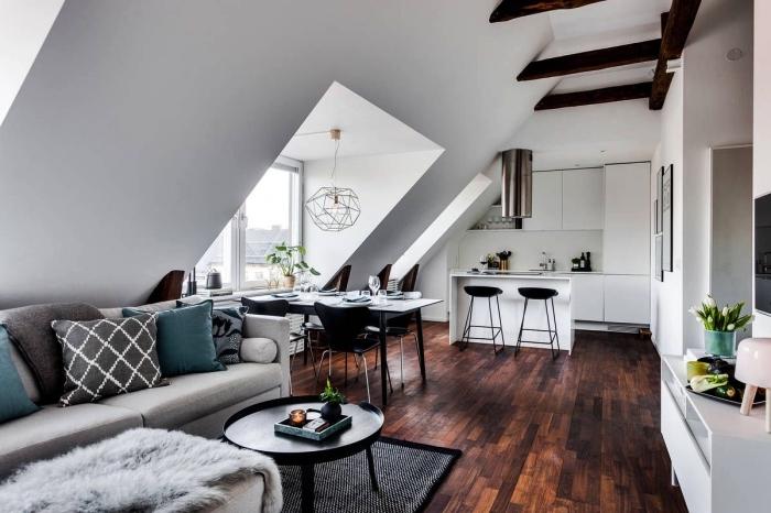 espace ouvert avec salon, cuisine et salle à manger, une chambre sous comble au design scandinave avec une cuisine blanche sur mesure
