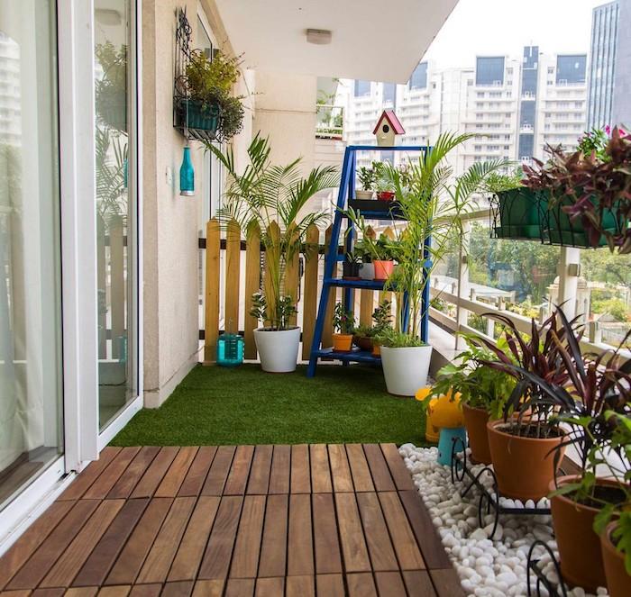 revêtement sol de balcon en bois, galets et gazon artificiel, petite palissade bois, étagère pour plantes escabeay, plusieurs pots de fleurs pour un balcon fleuri, cadre urbain paysage