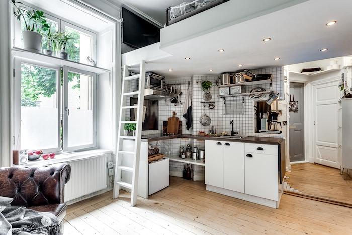 idée comment aménager une petite cuisine en meuble cuisine blanc et carrelage metro blanc, mezzanine lit adulte, fauteuil en cuir marron, parquet bois blond