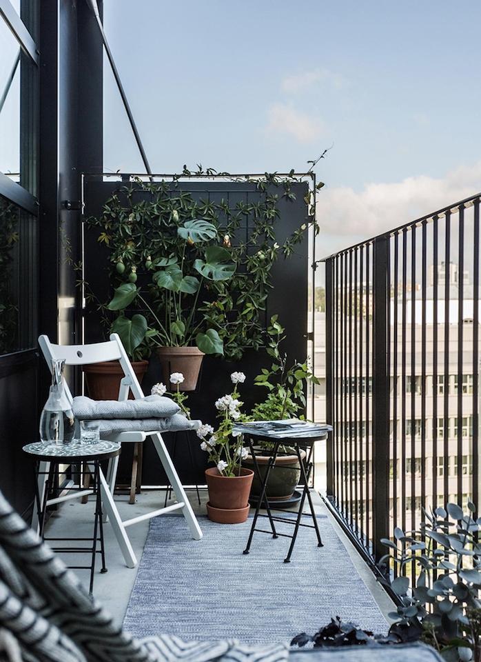 idée d aménagement petit balcon style scansinave avec chaise bois blanche, tables basses noires, plantes vertes en pot, garde corps noir