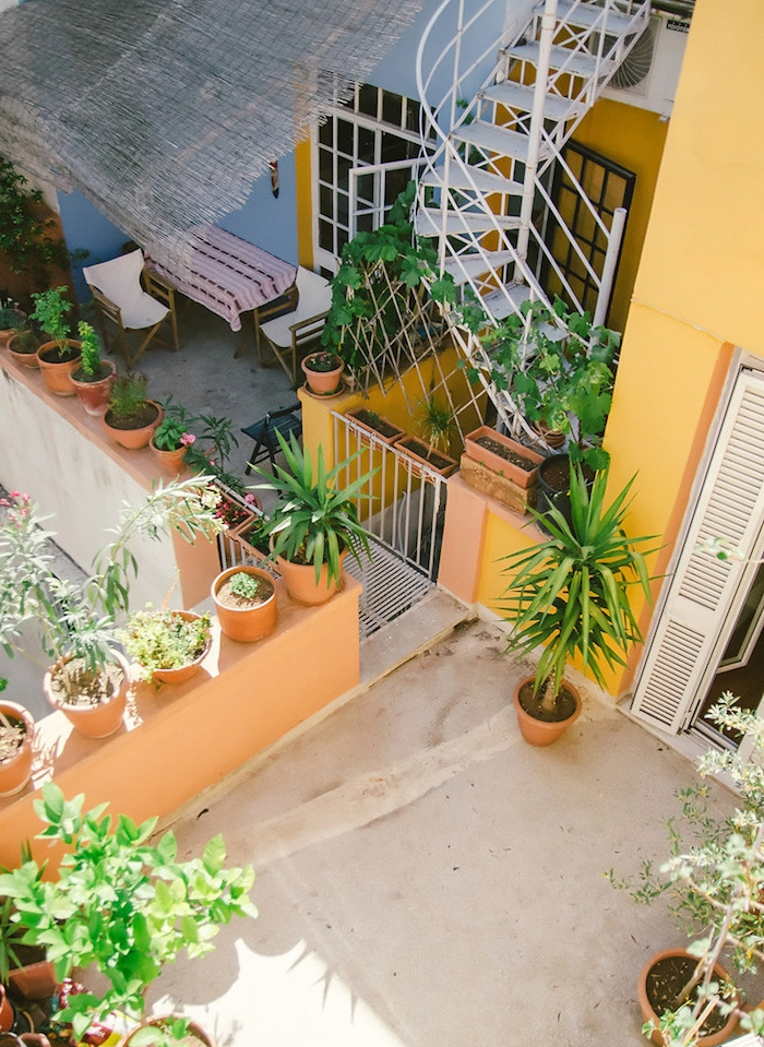 plusieurs pits de fleurs sur un balcon assez spacieux, escalier en colimaçon, coin repos avec table et chaises avec couverture