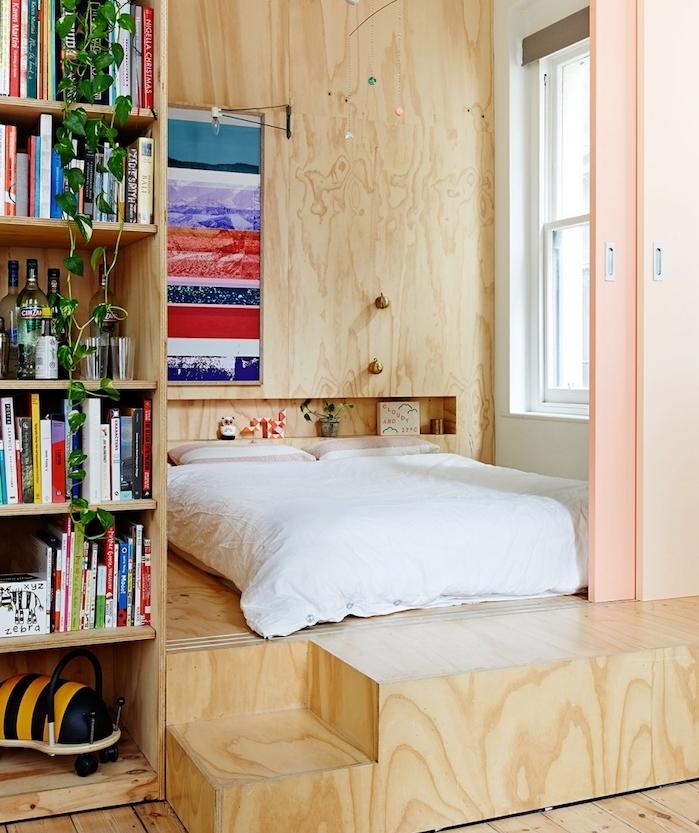lit en simple matelas sur estrade de bois avec bibliothèque à coté, niche murale dans mur de bois, portes coulissantes de separation