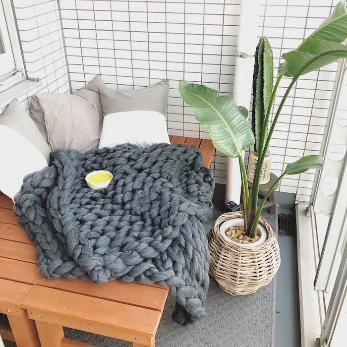 aménagement petit balcon dans style japonais, carrelage blanc sur les murs, canapé bois avec plaid moelleux et coussins gris, plante exotique dans cache pot en osier