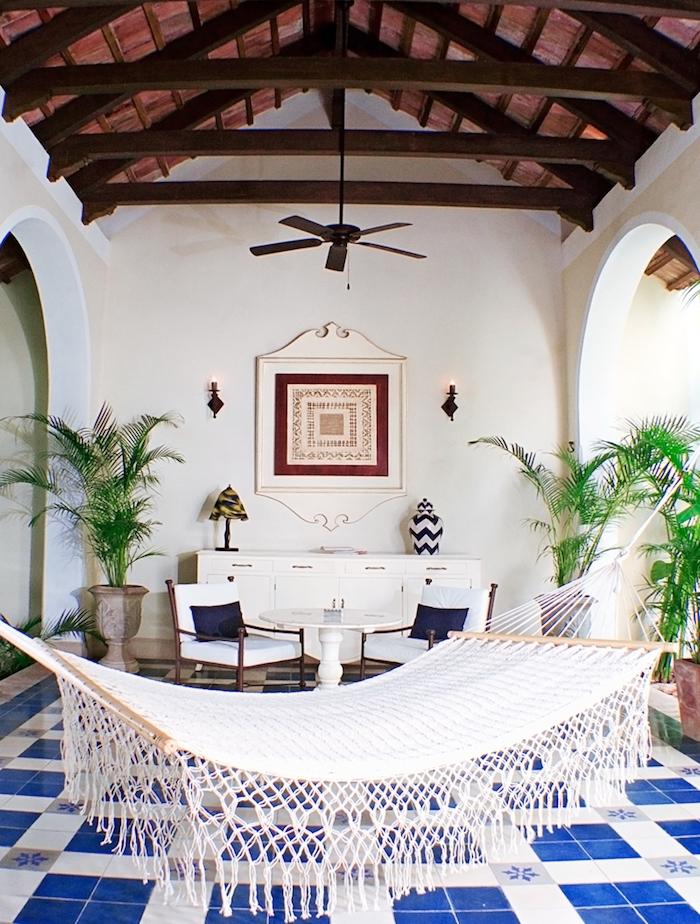 balcon couvert avec toiture en bois, hamac d exterieur, carrelage sol bleu et blanc, meuble blanc, table et chaises pour constituer un coin repos, plantes exotiques en pots