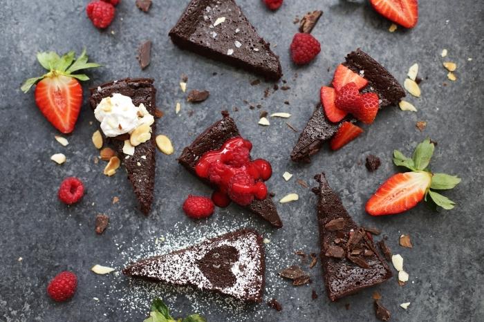 gateau au chocolat sans farine et sans lactose décoré de morceaux de fraises et d'amandes effilées, recette de gâteau vegan au chocolat et à la sauce de framboises express
