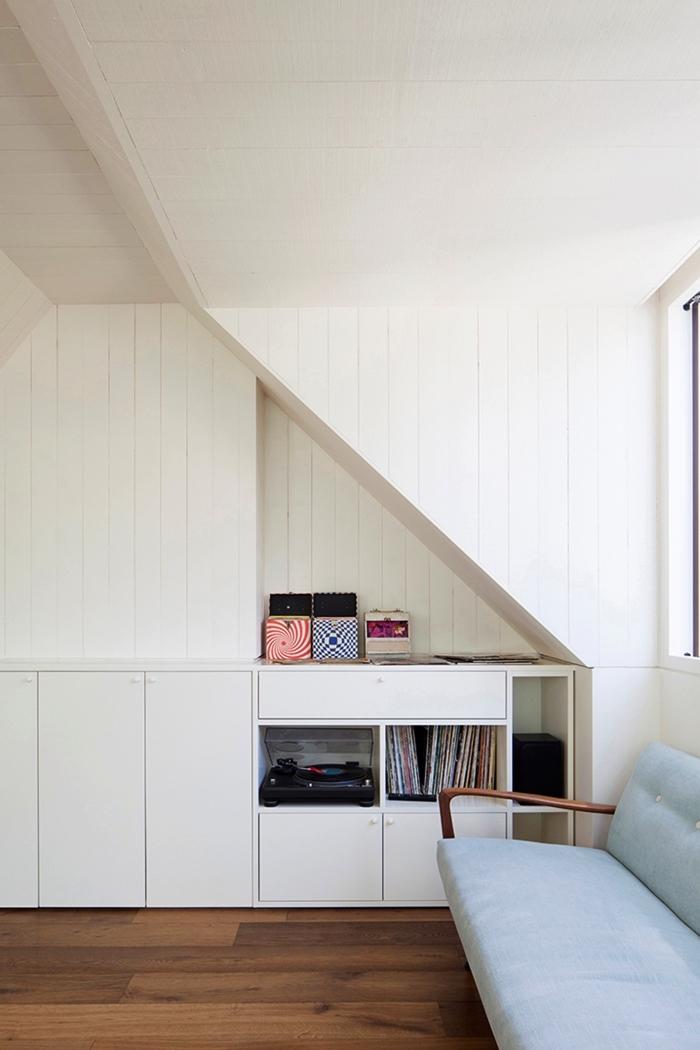 un meuble de rangement sous pente avec niche murale qui offre un espace supplémentaire, coin perdu optimisé dans une chambre sous comble