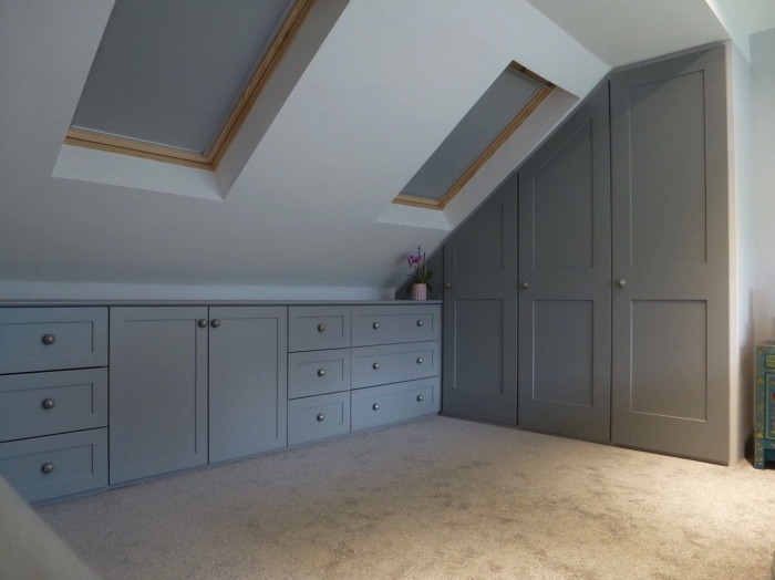 une chambre sous combles avec meubles de rangement sur mesure, placard et armoire sous pente encastrés
