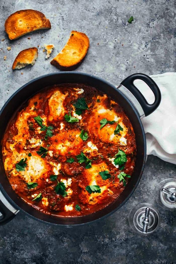 repas du soir simple, des oeufs pochés à la sauce tomate et poivron épicée à déguster à même la poêle