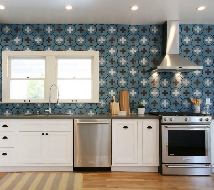 carrelage imitation carreaux de ciment aux motifs graphiques vintage en bleu canard qui recouvre le mur entier