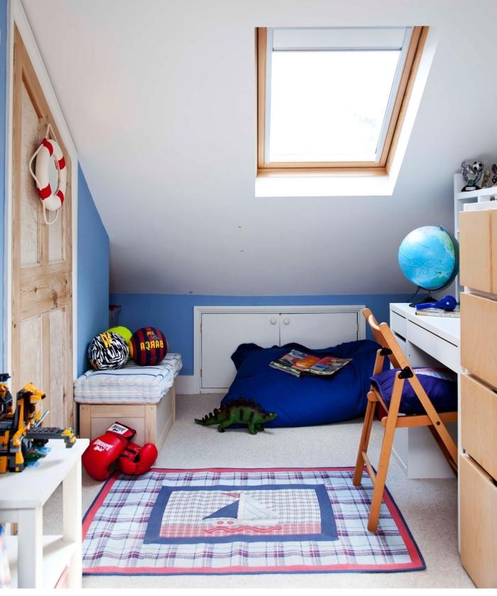 placard sous pente discret et une banquette basse dans une chambre d'enfant mansardée en bleu et blanc