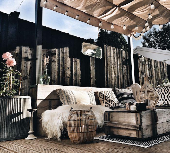 salon de balcon dans style boheme chic, avec canapé bois et table bois recyclé, bougeoirs orientaux vintage, pergola metal et toile, guirlande ampoules lumineuse, tapis noir et blanc