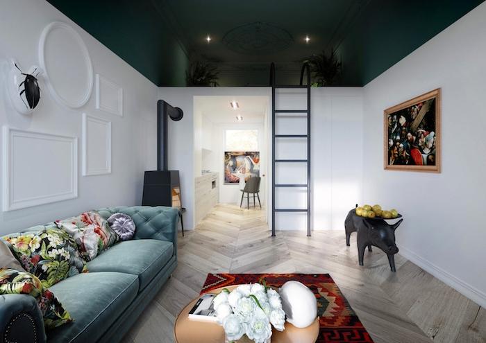plafond couleur vert foncé et murs blancs, petite cuisine en blanc, grand canapé bleu paon décoré de coussins fleuris, tapis coloré, murs décoré de tableaux d art