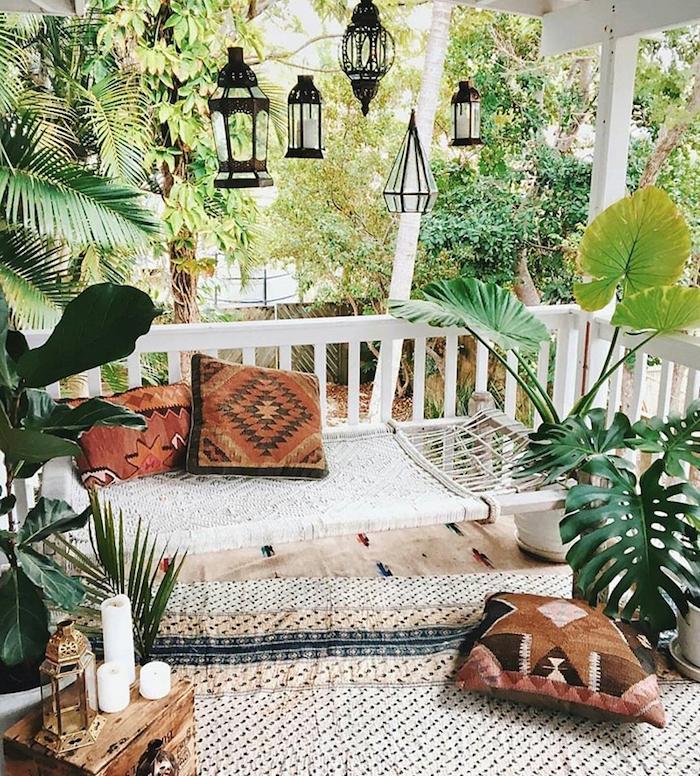 décorer sa terrasse dans style boheme avec hamac d exterieur avec coussins orientaux, tapis cocooning, deco de bougies, plantes exotiques d exterieur, lanternes noires suspendues