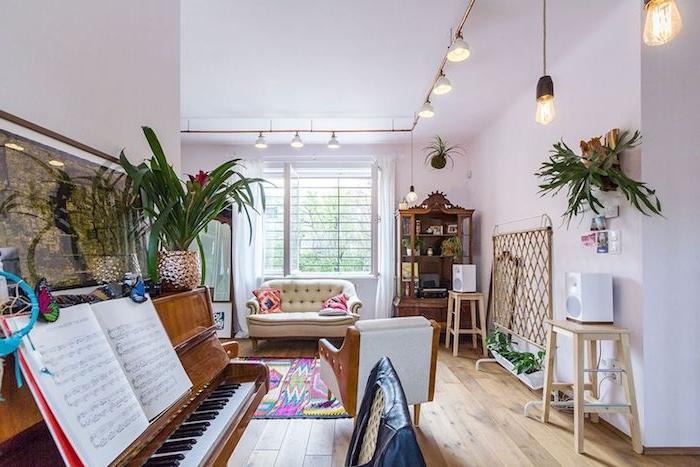 espace de divertissement avec piano ouvert sur salon avec canapé blanc cassé, parquet bois clair, suspensions éclairage original, mobilier ancien exotique