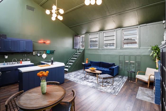 murs vert olive, cuisine, ilot central et canapé bleu foncé, parquet marron foncé, table bois ronde entourée de chaises anciennes, tapis gris et blanc